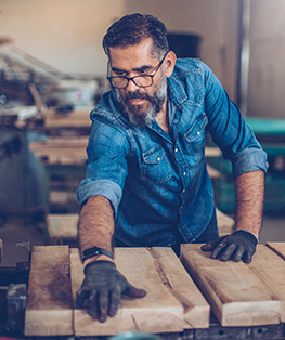 middle aged man woodworking with eye glasses